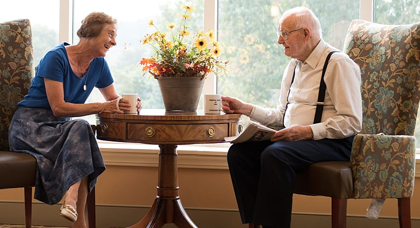 Retired couple enjoying morning coffee by a window