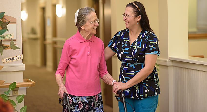 Landis at Home employee and retired women enjoying conversation while walking down a hallway