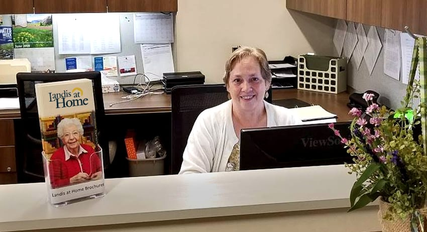 Landis at Home employee smiling from behind reception desk