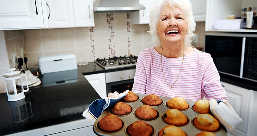 Retired woman happily baking muffins