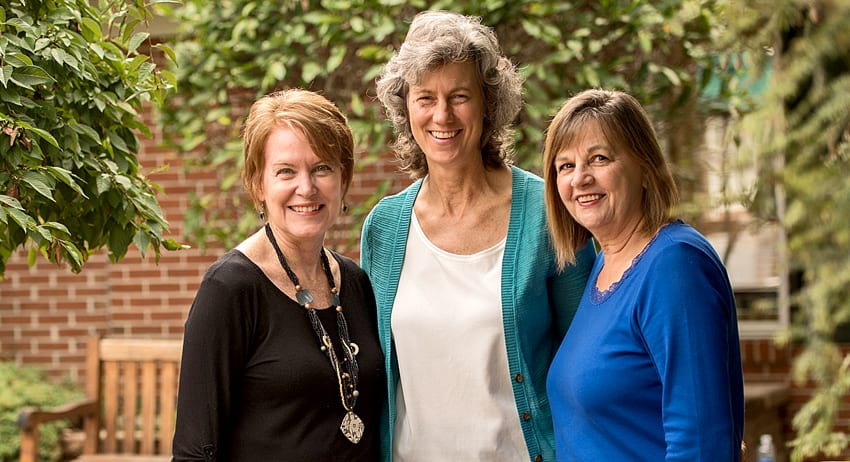 Three Landis at Home staff smiling for group photo in courtyard