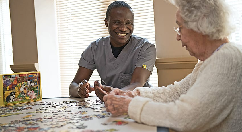 Landis at Home employee and retired women, enjoying working on a puzzle together