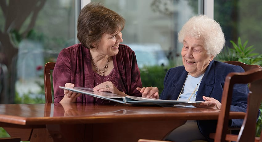 Landis at Home employee reviewing a packet of information with retired woman