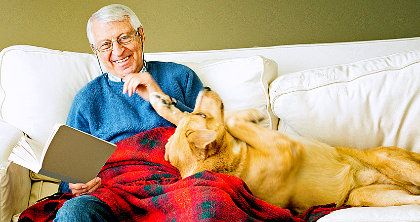 Retired man reading on couch, next to dog