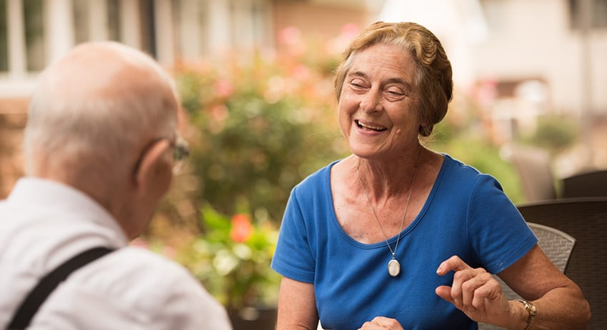 A retired couple, enjoying conversation in an outdoor courtyard