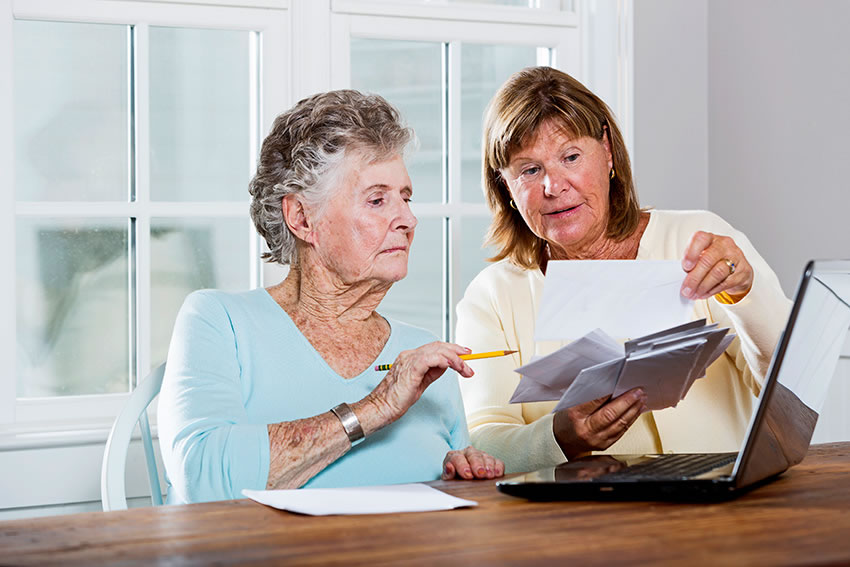 Landis at Home employee assisting retired woman to review and address a pile of bills and statements