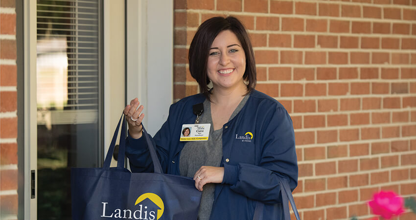 Landis at Home employee deliverying a bag of goods to house