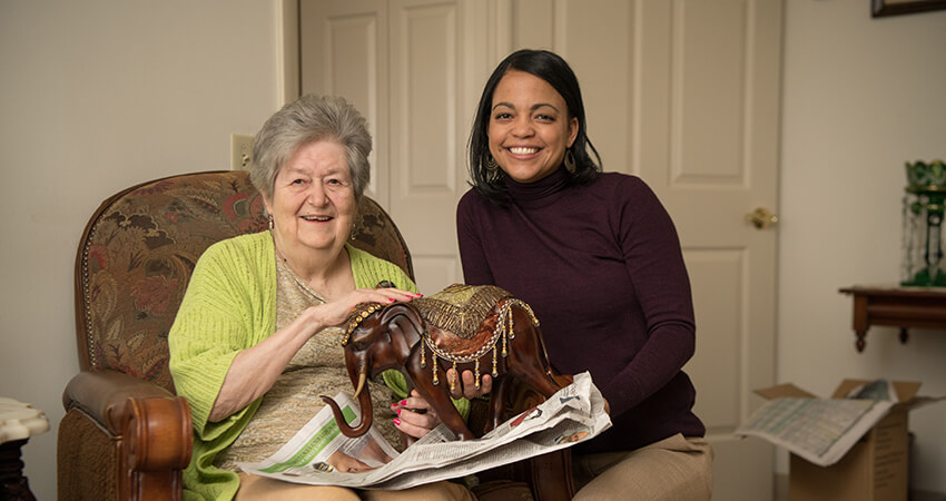 Woman smiling while showing off an heirloom elephant statue
