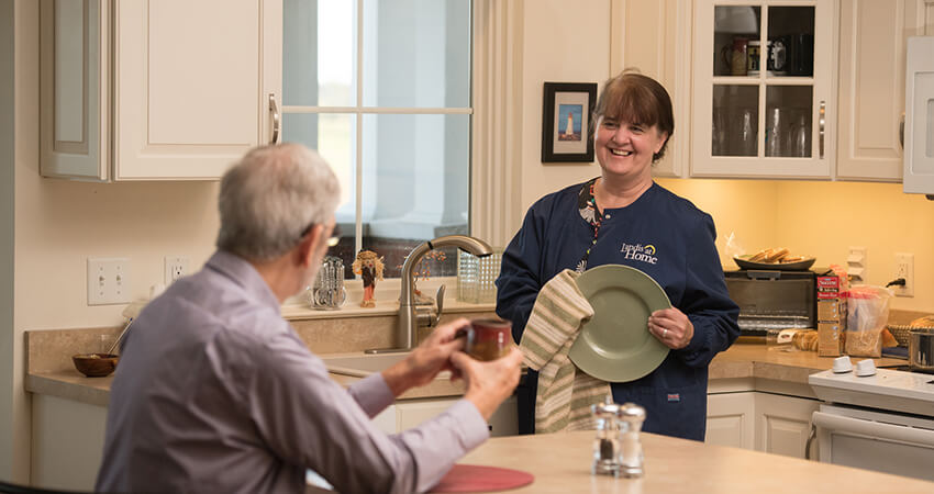 Landis at Home employee smiling while drying dishes and conversing with man